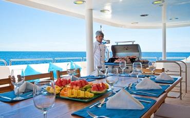 Disfruta de una comida deliciosa al aire libre en la cubierta exterior del yate Cormorant.